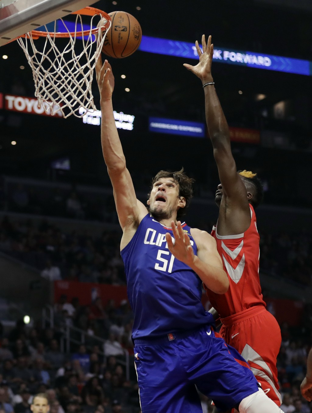Los Angeles Clippers' Boban Marjanovic (51) drives past Houston Rockets' Clint Capela during the first half of an NBA basketball game Sunday, Oct. 21,