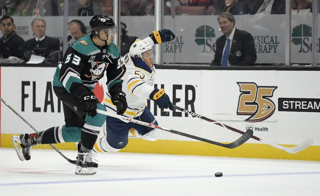Buffalo Sabres center Jeff Skinner, right, dives for the puck as Anaheim Ducks left wing Max Comtois takes it during the first period of an NHL hockey...