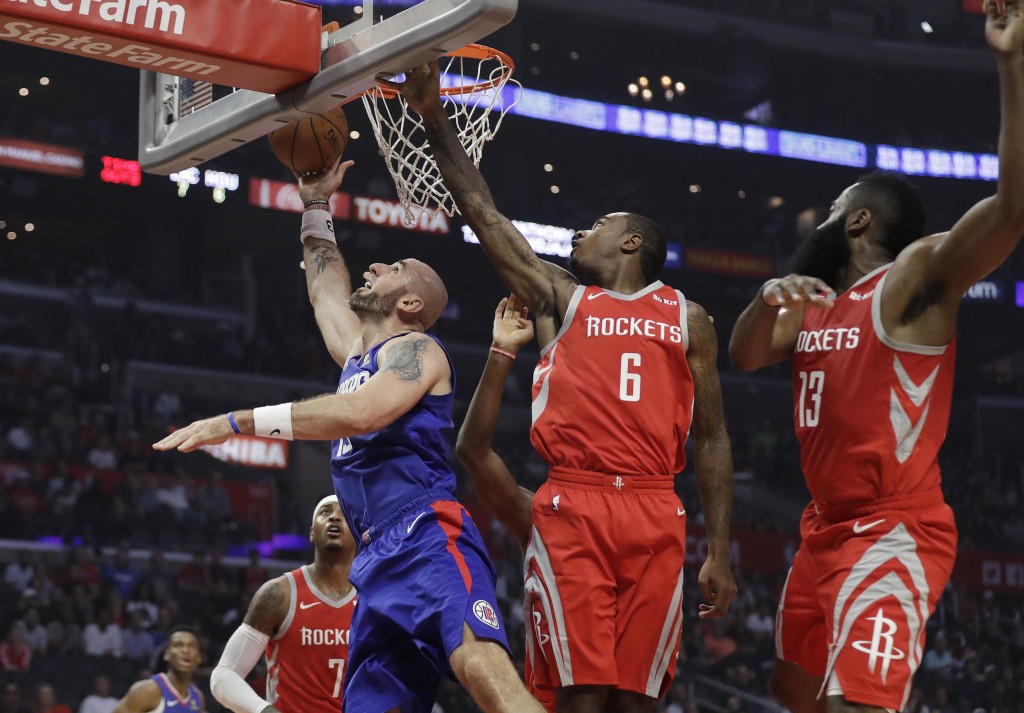 Los Angeles Clippers' Marcin Gortat, left, scores past Houston Rockets' Gary Clark (6) and James Harden (13) during the first half of an NBA basketbal...