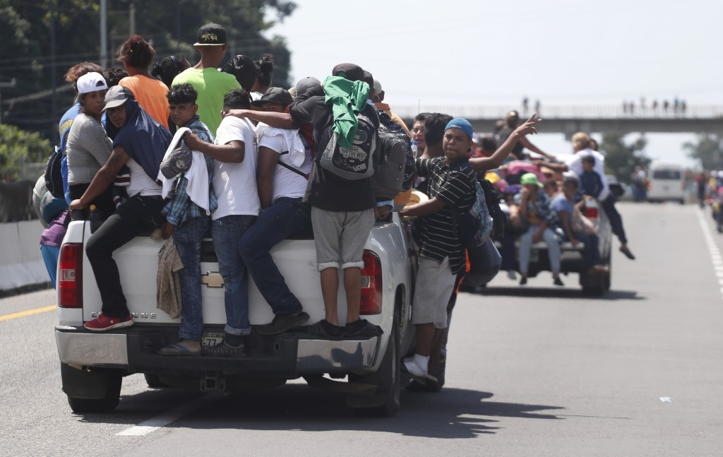 Central American migrants making their way to the U.S. in a large caravan cling to the trucks of drivers who offered them free rides, as they arrive t...