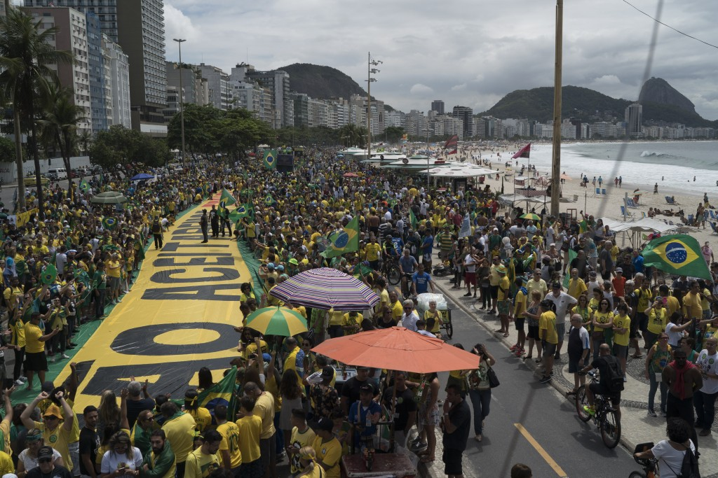 People rally in support of presidential candidate Jair Bolsonaro, of the far-right Social Liberal Party, backdropped by Sugarloaf Mountain in Copacaba...