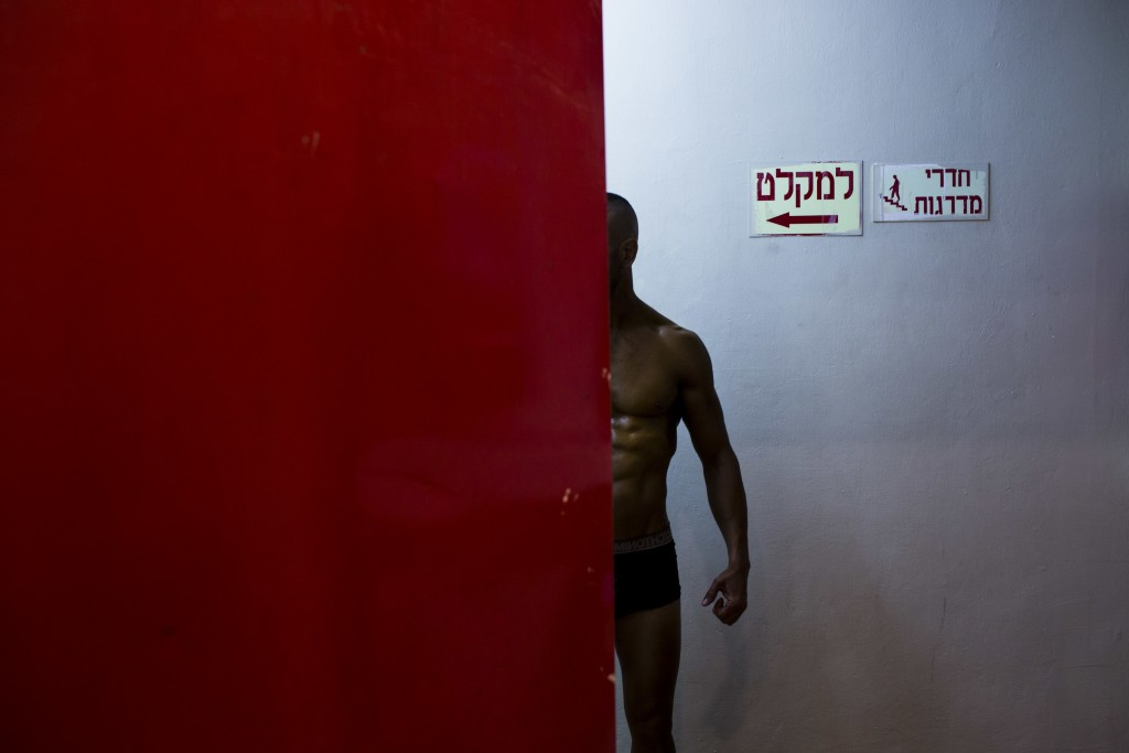 In this Thursday, Oct. 18, 2018 photo, a contestant has his body painted backstage  during the National Amateur Body Builders' Association competition