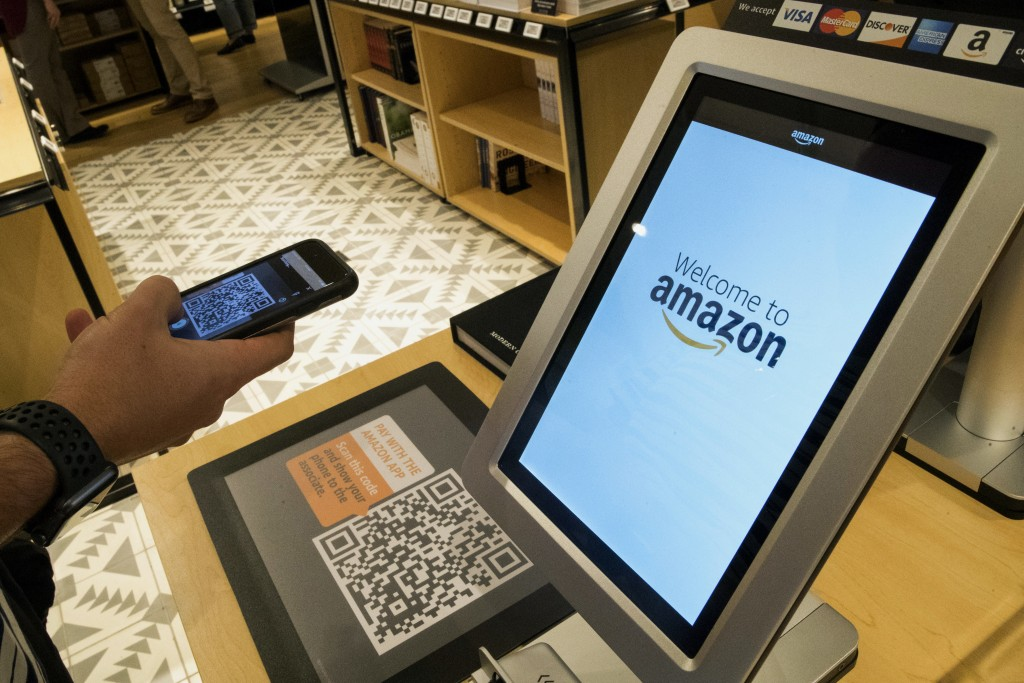 FILE- In this Sept. 27, 2018, photo Daniel Thorpe, of Hoboken, N.J., uses the Amazon app to pay for his purchase at the Amazon 4-star store in the Soh
