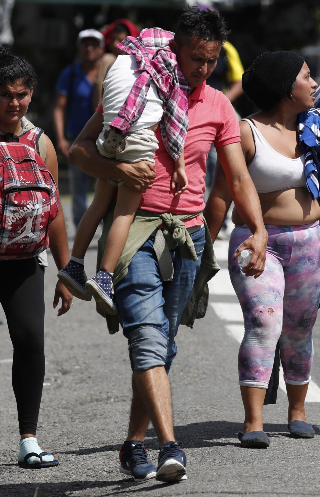 A Central American migrant carrying a child walks with a caravan making its way to the U.S., upon arrival to Tapachula, Mexico, Sunday, Oct. 21, 2018.