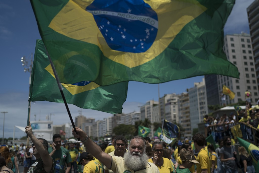 A man waves a Brazilian flag during a campaign rally for presidential candidate Jair Bolsonaro, of the far-right Social Liberal Party, in Copacabana, ...