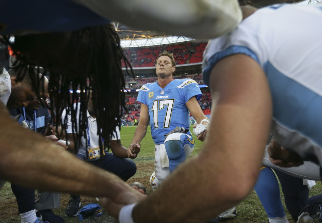Los Angeles Chargers quarterback Philip Rivers (17) joins other players in prayer after an NFL football game against Tennessee Titans at Wembley stadi