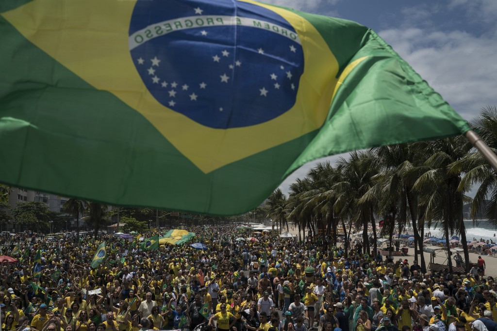 A Brazilian flag is waved by a supporter of presidential candidate Jair Bolsonaro, of the far-right Social Liberal Party, from a truck carrying sound