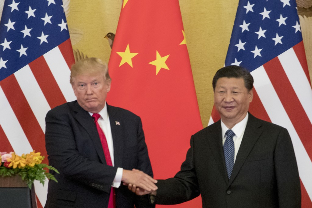 FILE - In this Nov. 9, 2017 file photo, President Donald Trump and Chinese President Xi Jinping shake hands during a joint statement to members of the