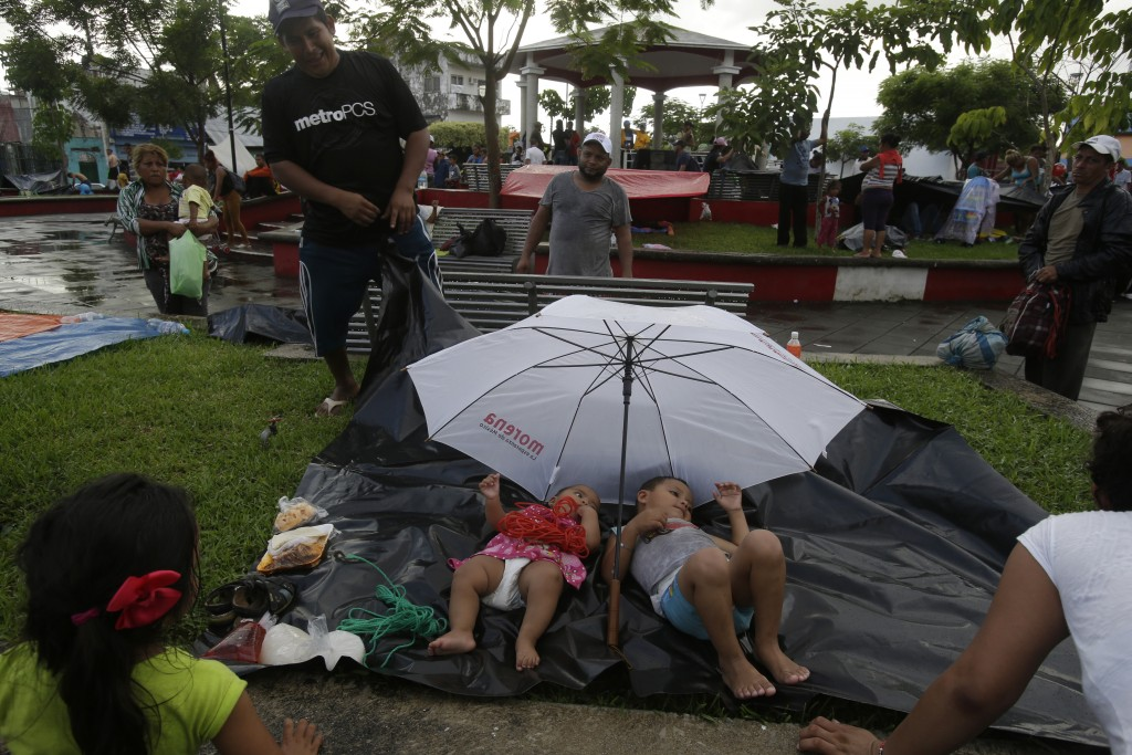 Central American children traveling with a caravan of thousands of migrants rest on a plastic tarp as their parents set up camp in a public park, afte...