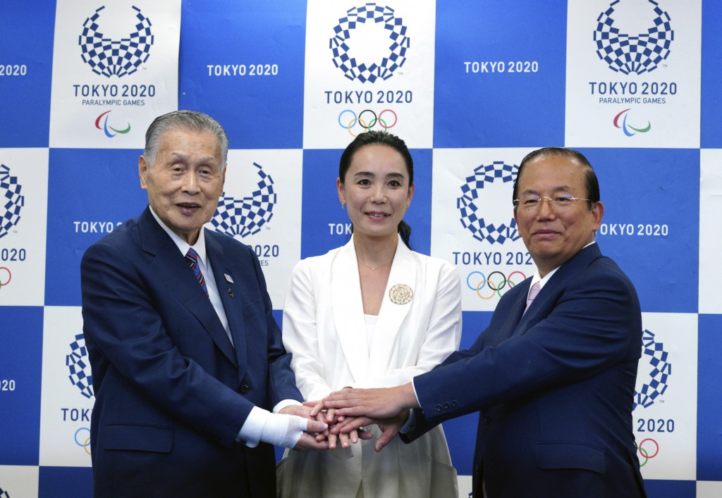 Japanese film director Naomi Kawase, center, Tokyo Olympic organizing committee President Yoshiro Mori, left, and Toshiro Muto, right, CEO of the Toky...