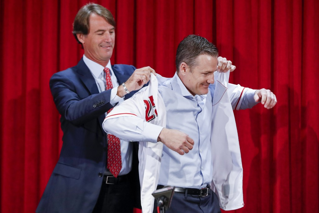 Cincinnati Reds manager David Bell, right, puts on his number 25 jersey with the help of Dick Williams, president of baseball operations, Monday, Oct.