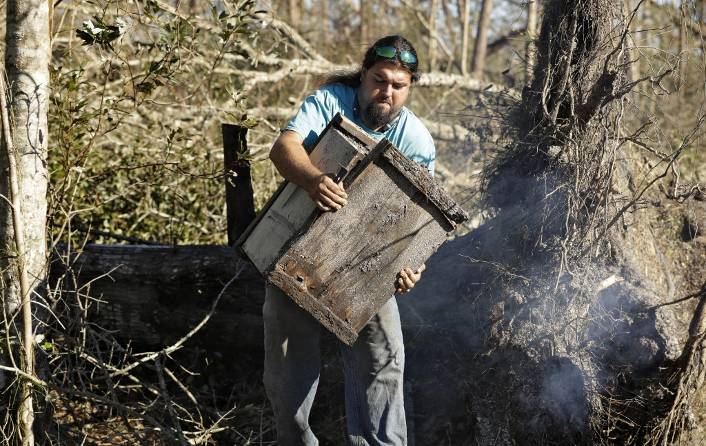In this Friday Oct. 12, 2018 photo, Justin Sours carries a beehive after a tree was knocked down by winds from Hurricane Michael in Wewahitchka, Fla. ...