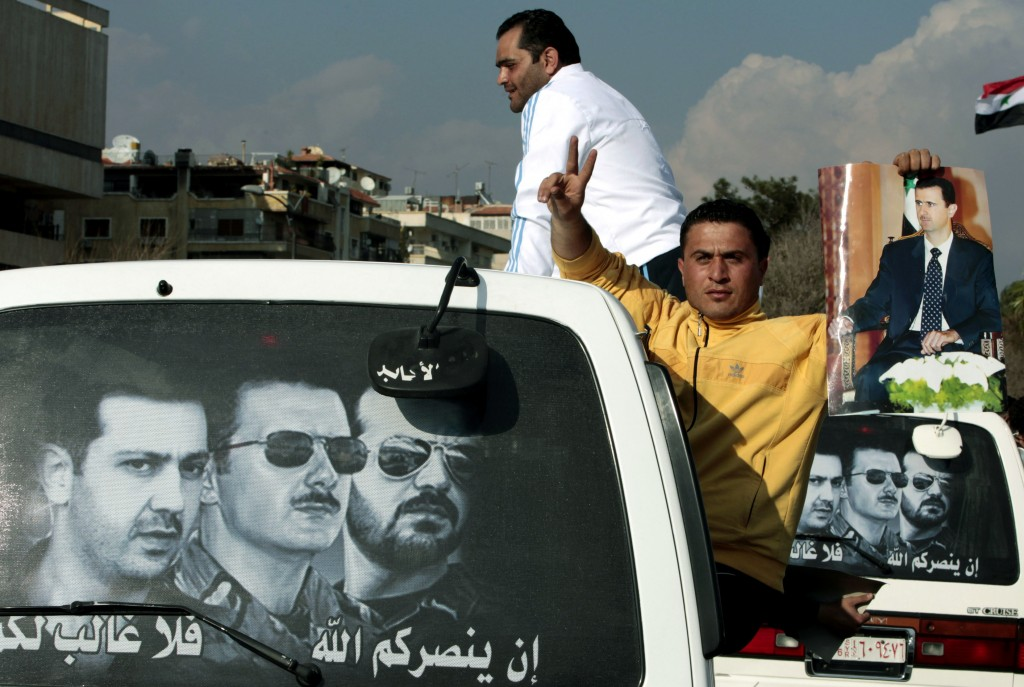 FILE - In this March 25, 2011 file photo, a man holds a picture of Syrian President Bashar Assad outside a mini van with a poster on the back showing