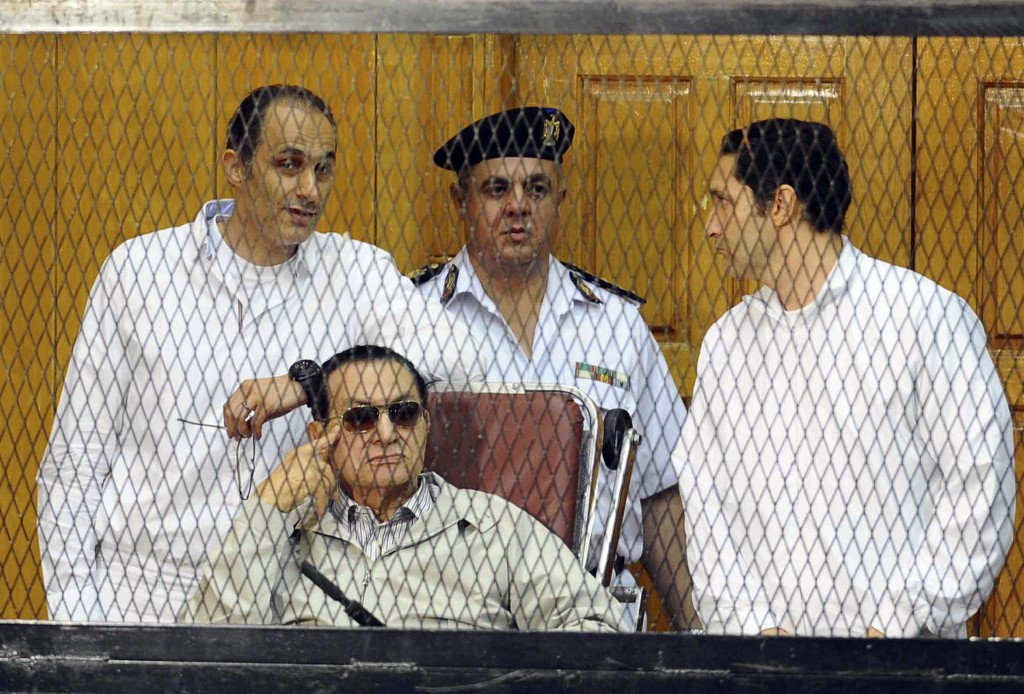 FILE - In this Sept. 14, 2013 file photo, former Egyptian President Hosni Mubarak, seated, and his two sons Gamal Mubarak, left, and Alaa Mubarak, rig