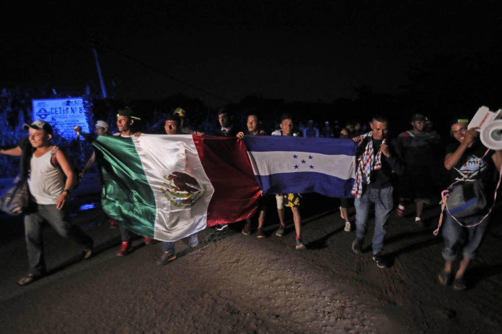 Central American migrants traveling with a caravan to the U.S. walk holding national flags from Mexico and Honduras as they make their way to Mapaste