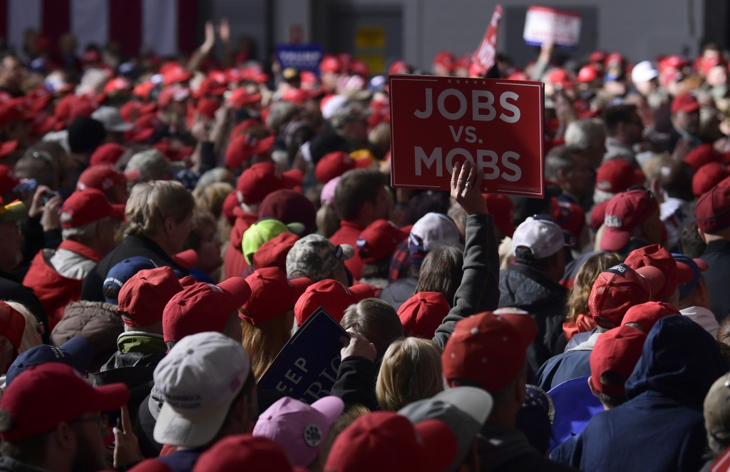 People listen as President Donald Trump speaks at a rally at Central Wisconsin Airport in Mosinee, Wis., Wednesday, Oct. 24, 2018. (AP Photo/Susan Wal...