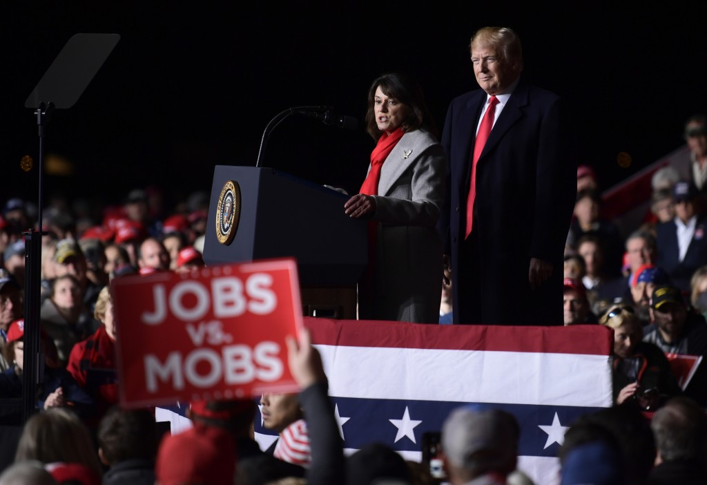 President Donald Trump, right, listens as Republican Senate candidate Leah Vukmir, left, speaks during a rally at Central Wisconsin Airport in Mosinee...