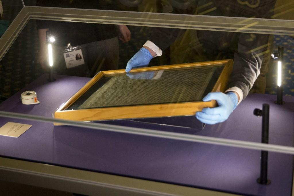 FILE - In this file photo dated Thursday, Feb. 5, 2015, The Salisbury Cathedral 1215 copy of the Magna Carta is installed in a glass display cabinet m...