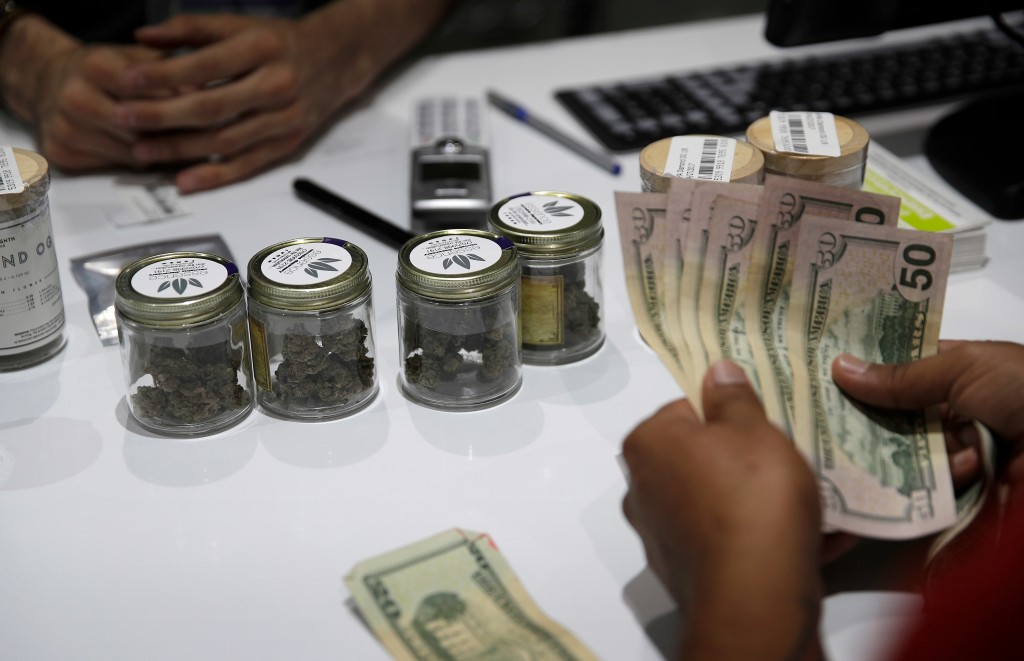 FILE - In this July 1, 2017, file photo, a person buys marijuana at the Essence cannabis dispensary in Las Vegas. The first full year of legalized mar...