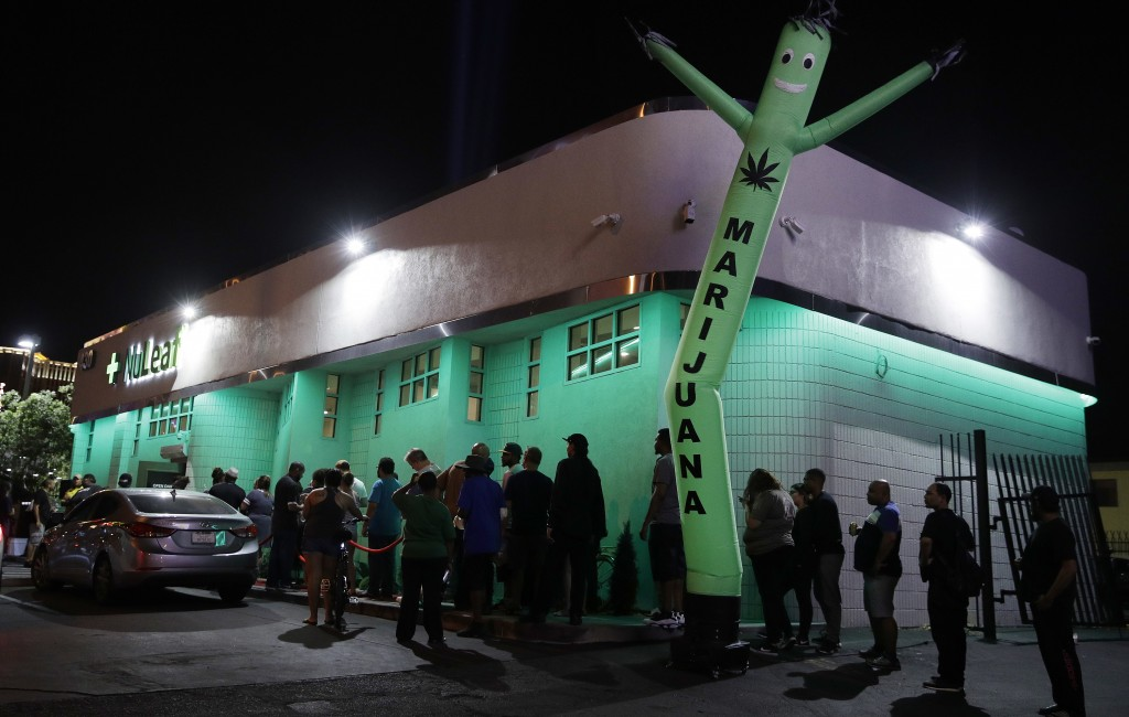 FILE- In this July 1, 2017, file photo, people line up at the NuLeaf marijuana dispensary in Las Vegas. A marijuana trade group says pot production, p...