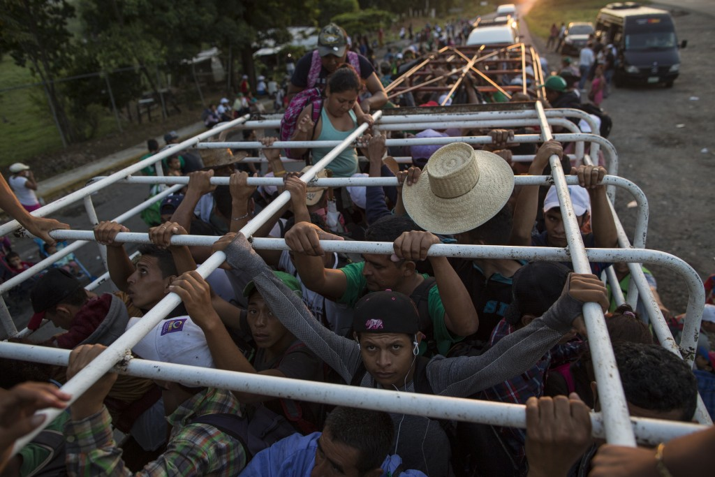Migrants travel on a cattle truck, as a thousands-strong caravan of Central American migrants slowly makes its way toward the U.S. border, between Pij...
