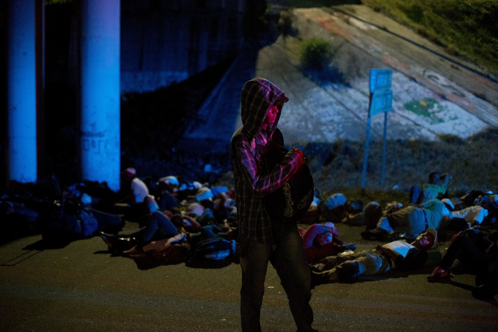 Central American migrants waiting for rides along the highway are lit by the lights of police cars providing security for them, as part of a thousands...