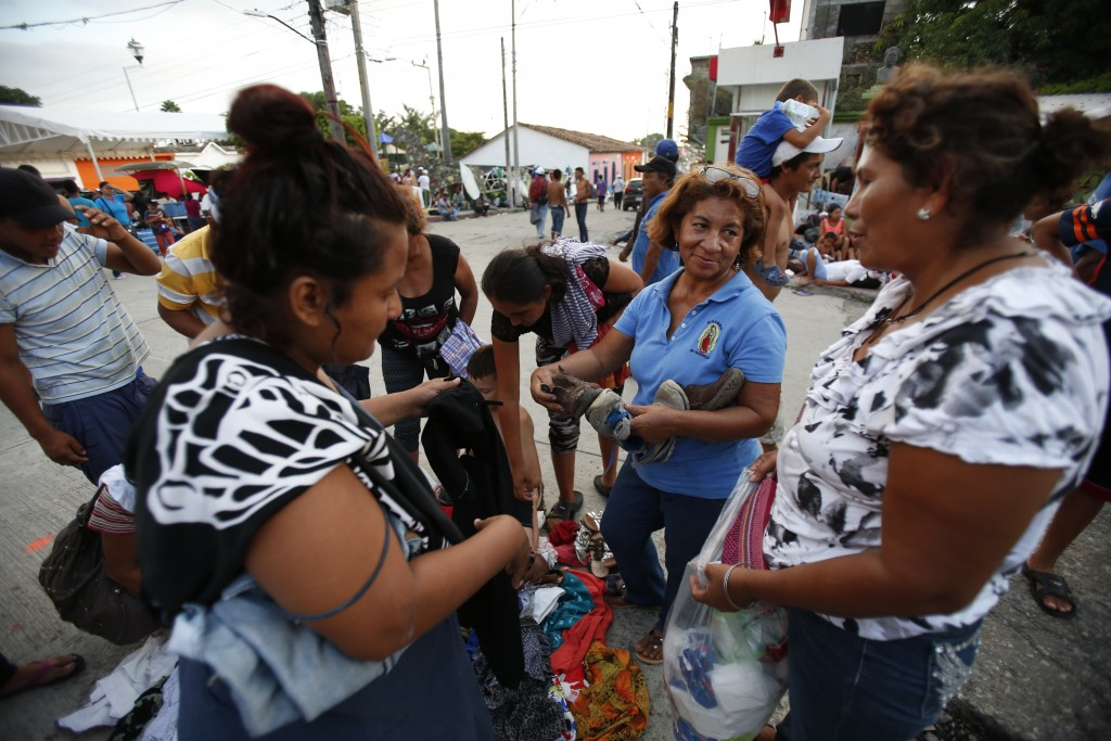 Central American migrants look through a pile of donated clothes, as a thousands-strong caravan of migrants prepares to camp out for the night in Piji...