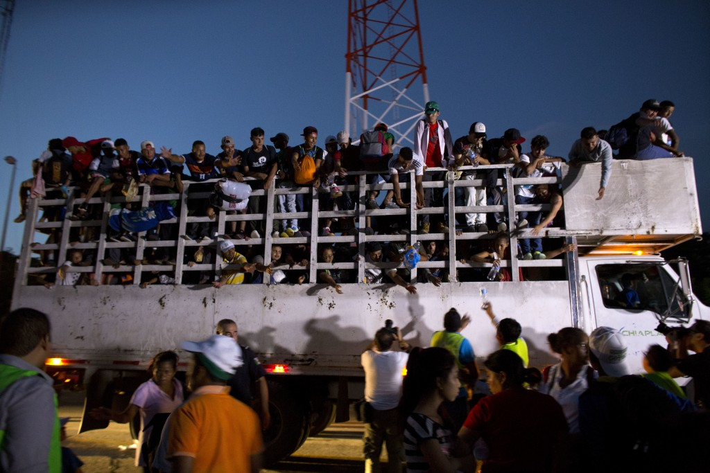 Men pass up water to Central Americans riding on the back of a truck while other migrants wait for rides, as a thousands-strong caravan of Central Ame...