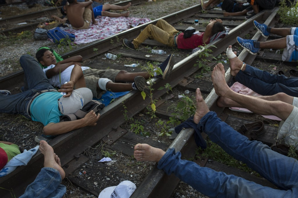 Migrants rest on the railroad rails, as a thousands-strong caravan of Central American migrants slowly makes its way toward the U.S. border, between P...