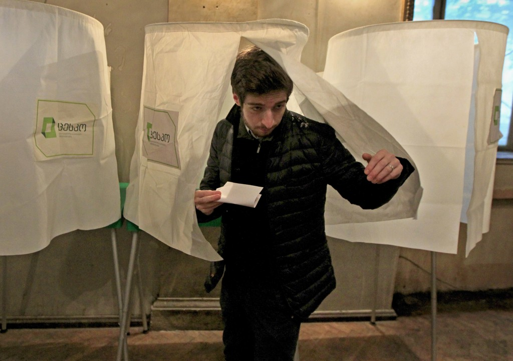 FILE - In this Oct. 30, 2016, file photo, a man leaves a voting booth during a parliamentary election runoff in Tbilisi, Georgia. Oct. 28, 2018's elec...