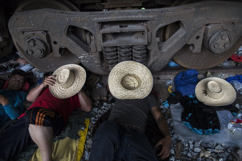 Migrants rest on the railroad rails as a thousands-strong caravan of Central American migrants slowly makes its way toward the U.S. border, between Pi...