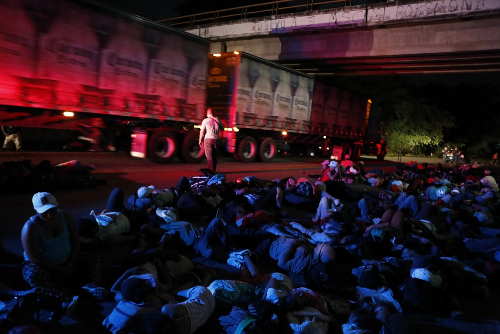 Scores of Central American migrants waiting for rides rest along the highway as they travel with a thousands-strong caravan slowly making its way towa...