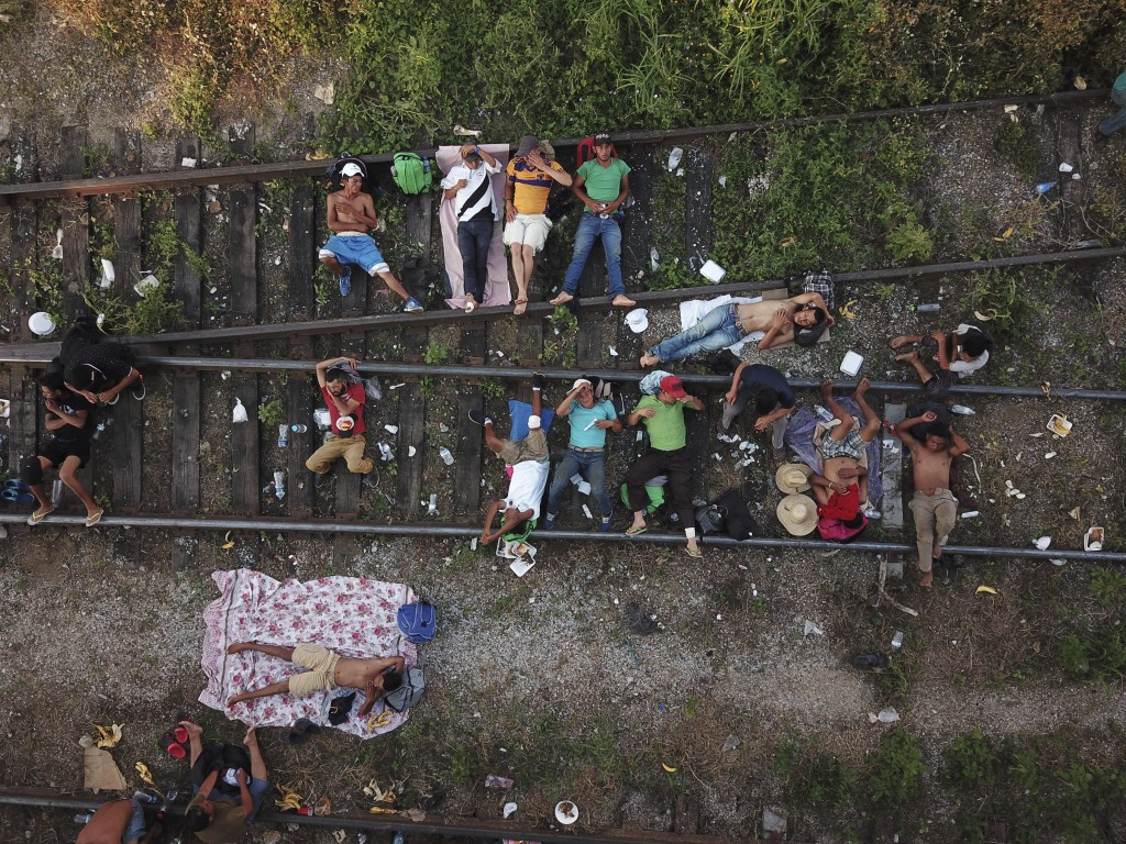 Migrants, who are part of a caravan of Central American migrants slowly makes its way toward the U.S. border, rest on the rails in Arriaga, Mexico, Fr...