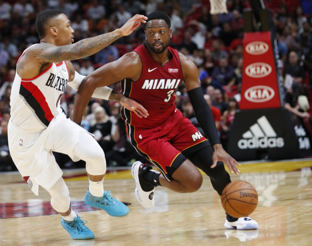 Miami Heat guard Dwyane Wade (3) drives to the basket against Portland Trail Blazers guard Damian Lillard (0) during the first half of an NBA basketba...