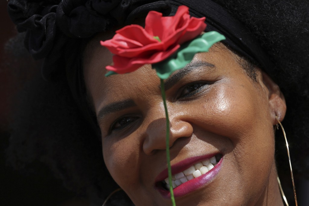 """A supporter of presidential candidate of the Workers' Party Fernando Haddad, shows her red rose during a """"March of Women for Haddad,"""" campaign rally a..."""