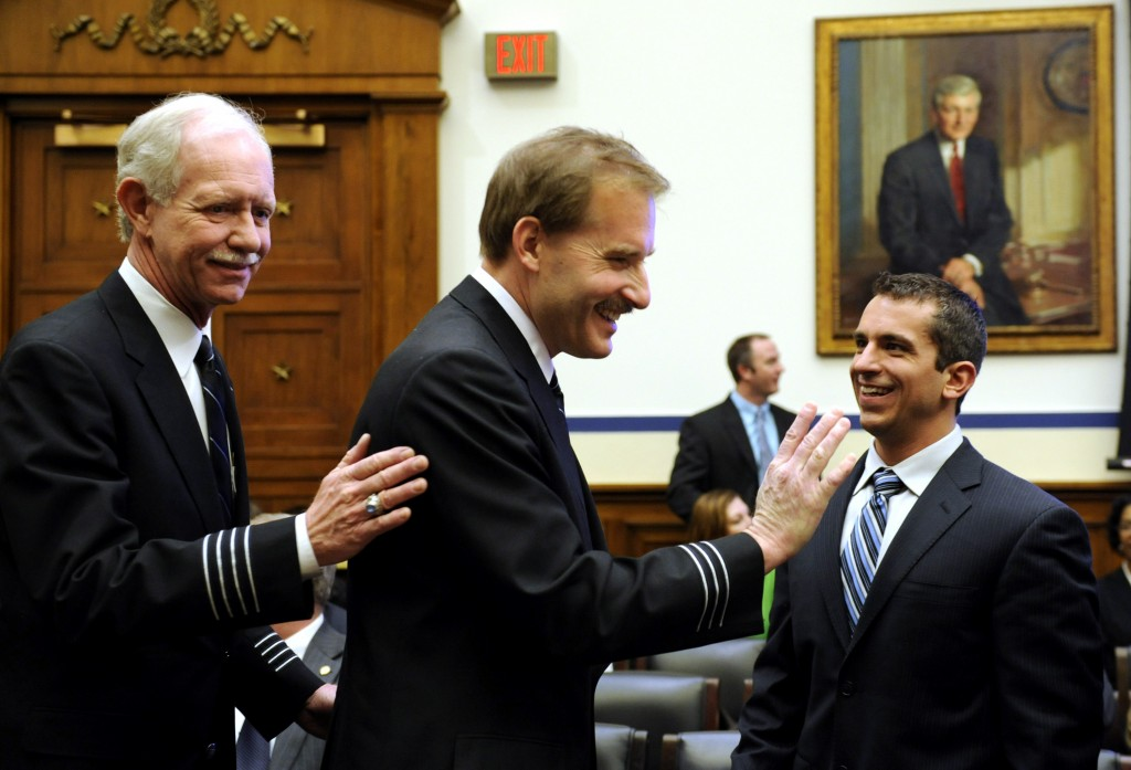 FILE - In this Feb. 24, 2009, file photo, Air Traffic Control Specialist Patrick Harten, right, smiles as US Airways flight 1549 Capt. Chesley B Sulle...