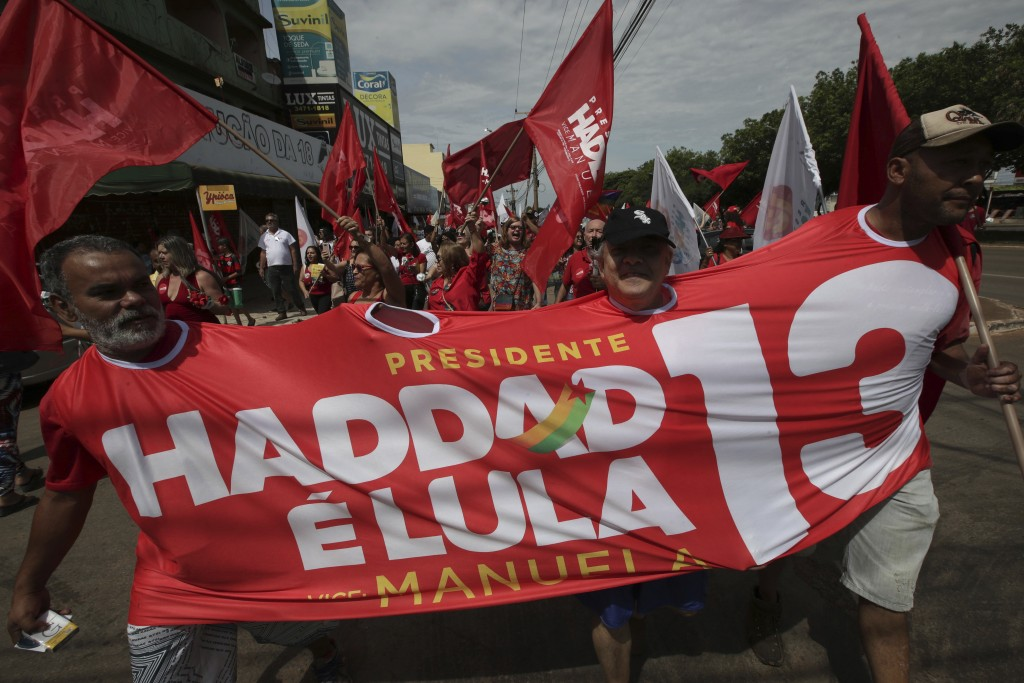 """Supporters of presidential candidate of the Workers' Party Fernando Haddad, dressed in a banner written in Portuguese """"Haddad is Lula 13"""", march durin..."""