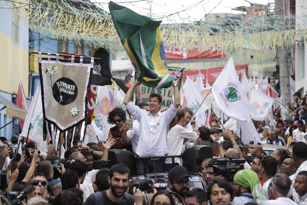 Fernando Haddad, Brazil's presidential candidate for the Workers' Party, holds a Brazilian flag during a campaign rally at the Heliopolis slum of Sao ...