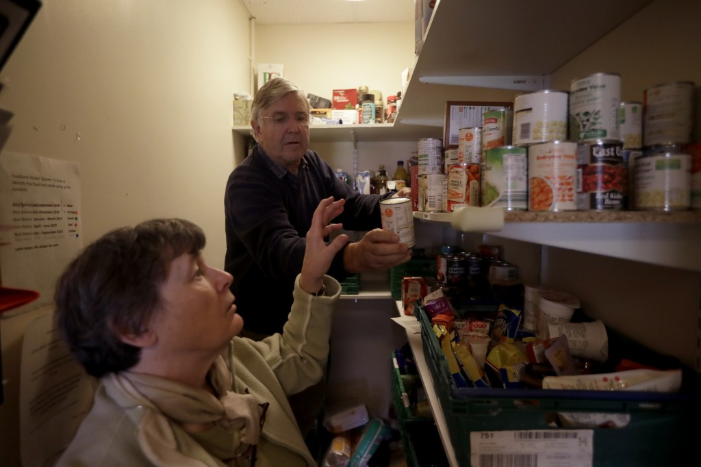 Volunteers Elizabeth and David gather food items from a checklist to give to a family from a foodbank at the Ivybridge estate community centre in west...