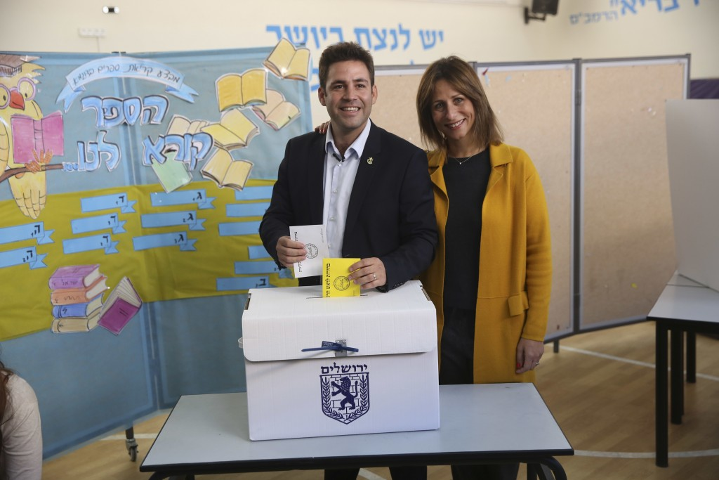 Mayoral candidate Ofer Berkovitch and his wife Dina pose for media as they cast their votes at a polling station during the municipal elections in Jer...