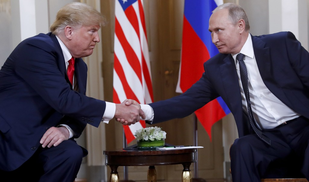 FILE - In this Monday, July 16, 2018, file photo, U.S. President Donald Trump, left, and Russian President Vladimir Putin shake hands at the beginning