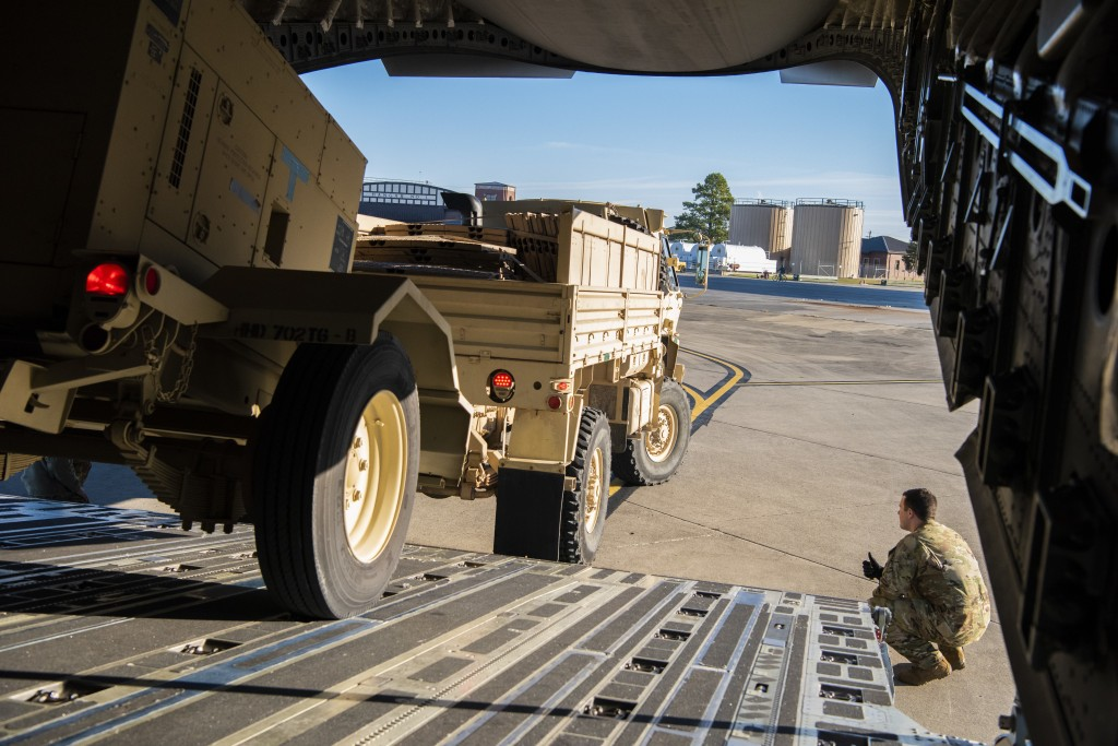 This Oct. 29, 2018 photo provided by the U.S. Air Force shows Airman 1st Class Trevor Pearce helping guide a military vehicle into the cargo compartme...