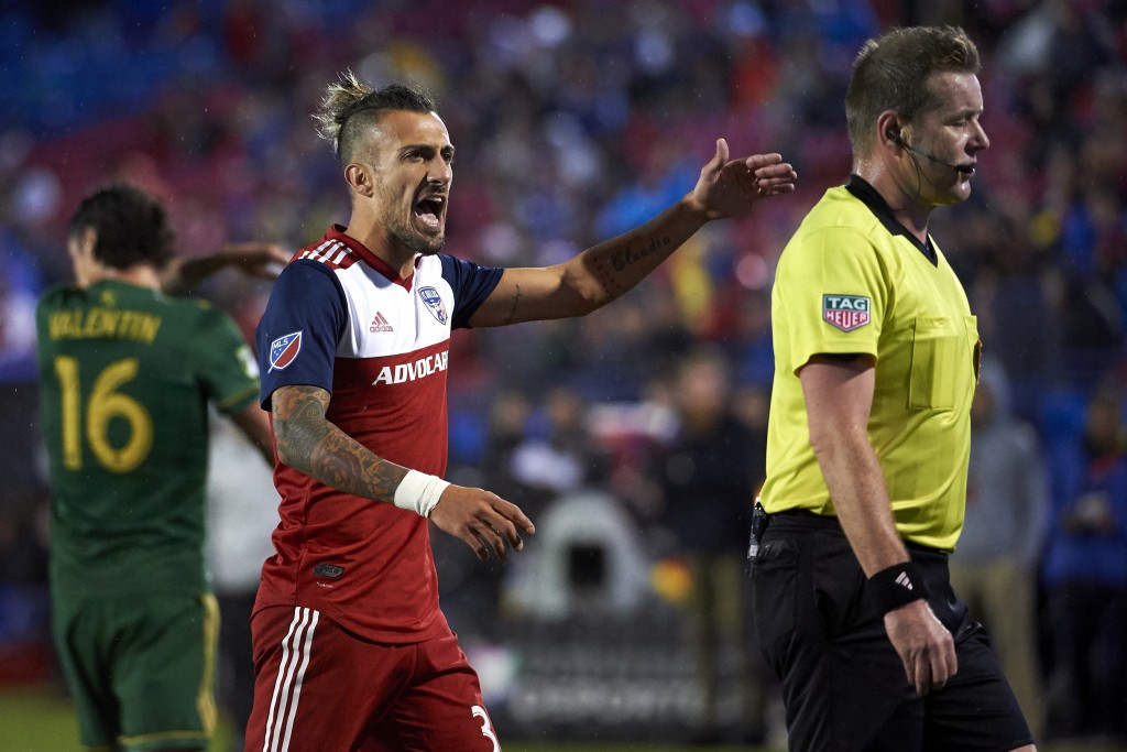 FC Dallas forward Maximiliano Urruti (37) has words with referee Alan Kelly during the first half of the team's MLS soccer playoff match against the P...