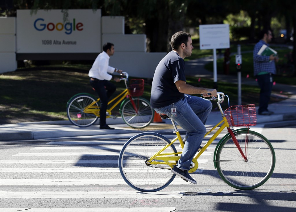 FILE - In this Oct. 20, 2015 file photo, employees ride company bicycles outside Google headquarters in Mountain View, Calif. Hundreds of Google emplo