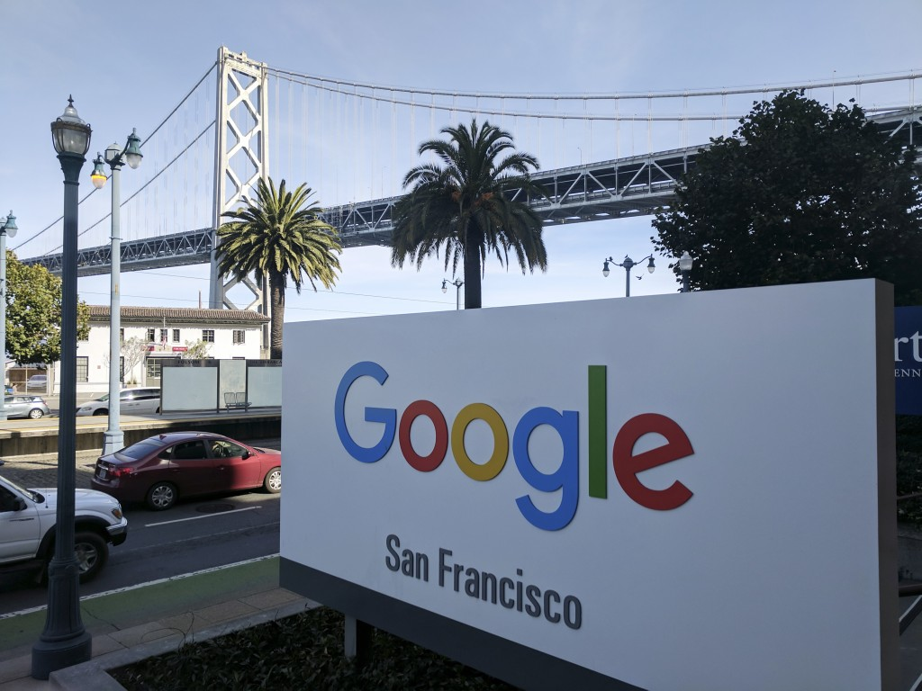 This photo shows signage outside the offices of Google in San Francisco with the San Francisco-Oakland Bay Bridge in the background, Wednesday, Oct. 3
