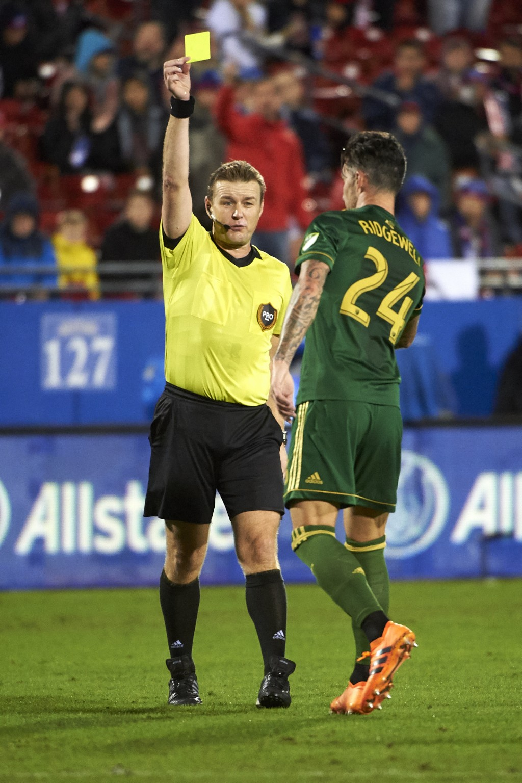 Portland Timbers defender Liam Ridgewell (24) receives a yellow card from referee Alan Kelly during the first half of an MLS soccer playoff match agai...
