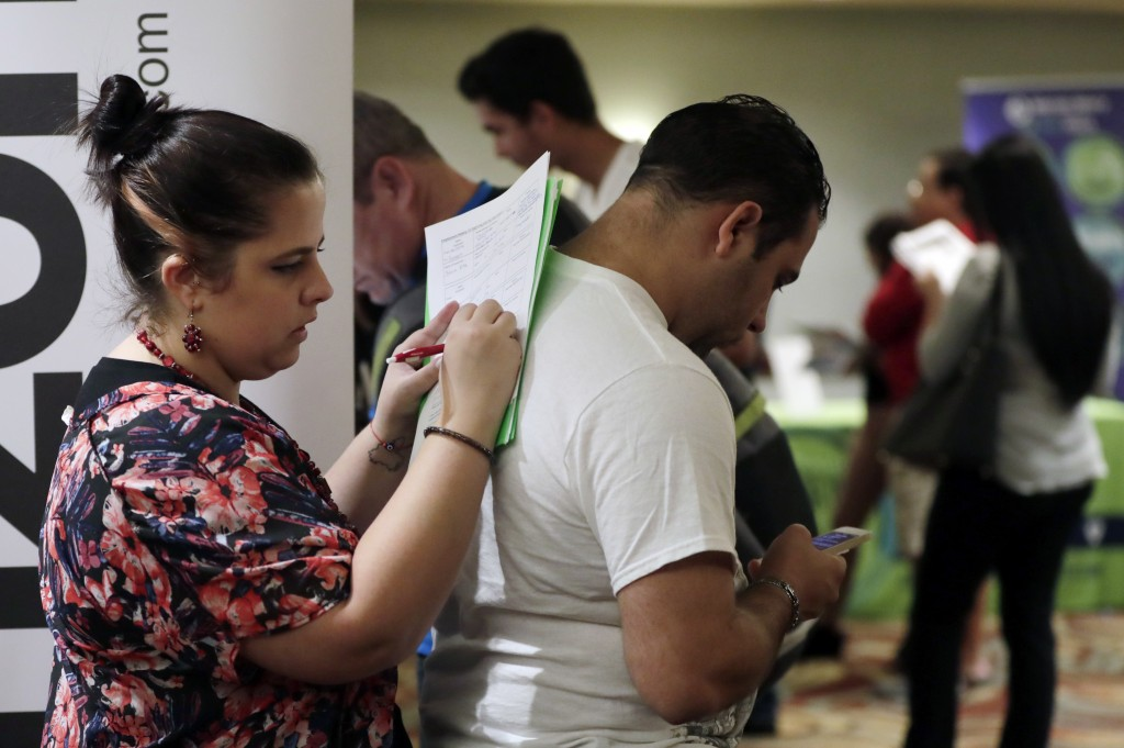 FILE- In this Jan. 30, 2018, file photo, Loredana Gonzalez, of Doral, Fla., fills out a job application at a JobNewsUSA job fair in Miami Lakes, Fla.
