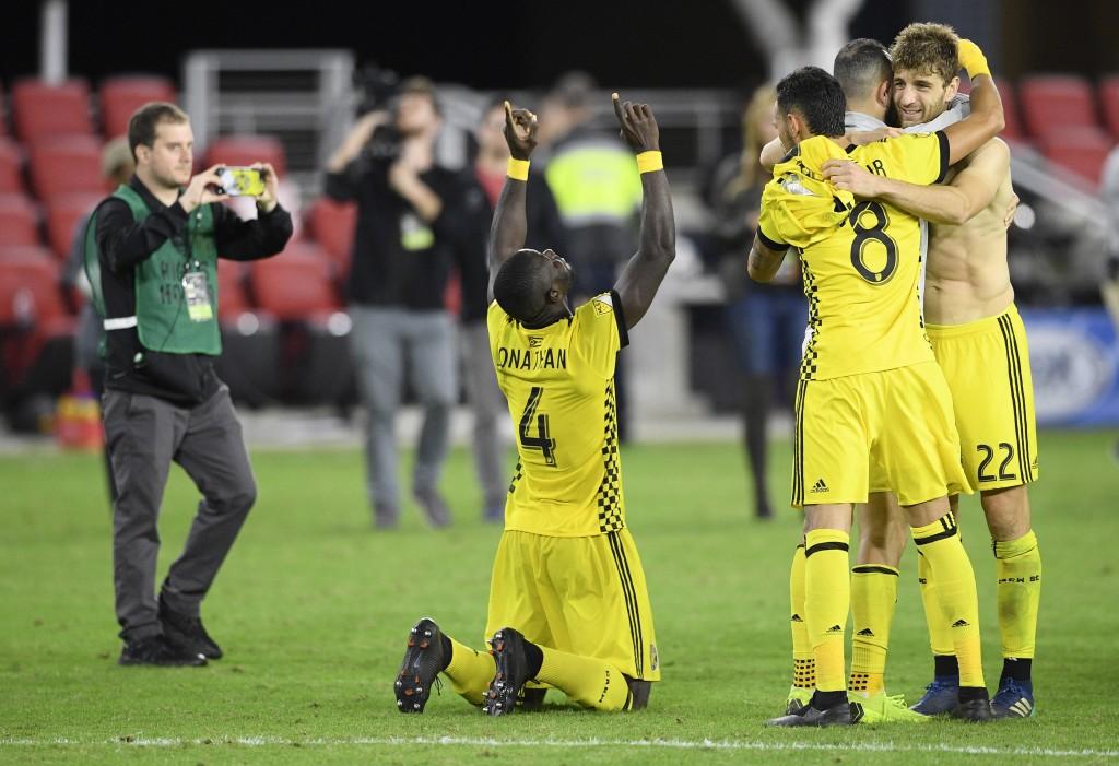 Columbus Crew SC defender Jonathan Mensah (4), midfielder Artur (8) and defender Gaston Sauro (22) celebrate after winning an MLS playoff soccer match...