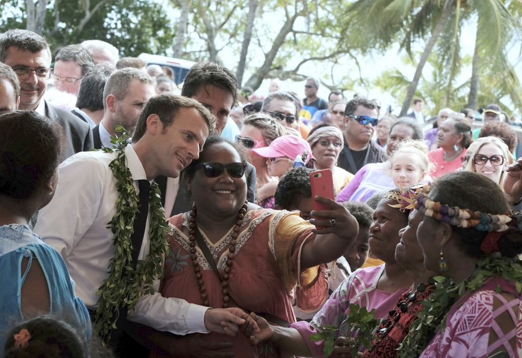 FILE - In this Saturday, May 5, 2018 file photo French President Emmanuel Macron, left, poses for a selfie while meeting residents as part of a rememb
