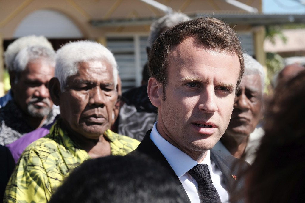 FILE - In this Saturday, May 5, 2018 file photo French President Emmanuel Macron is welcomed at Ouvea Island airport, off New Caledonia, before a reme...